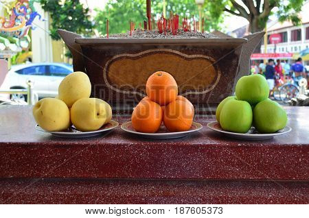 Fruits offering as a sacrifice at Chinese temple yellow pear orange and green apple