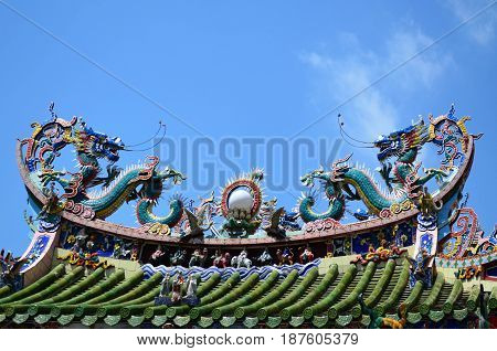 Two dragons statue on Chinese temple roof against blue sky
