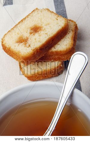 Black tea with sugar and cake with jam on a napkin