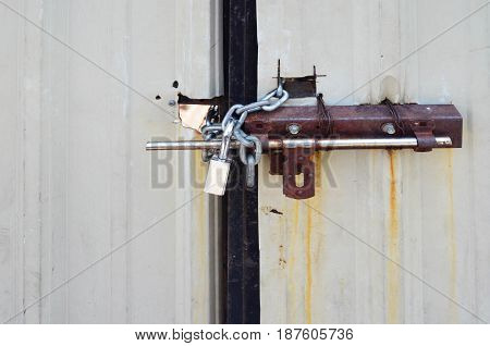 Locked padlock and chained on metal sheet gate