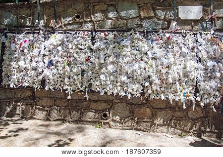 Wishing wall with tied note petitions to the Virgin Mary saint and Mother of God at her restored house near Ephesus Turkey