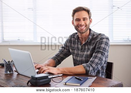 Young caucasian male student smiling at the camera with his hands on the keyboard of his laptop in front of him at his desk.