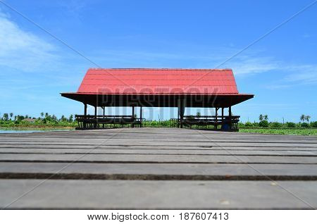 Red roof Thai pavilion with wooden bridge in lotus pond