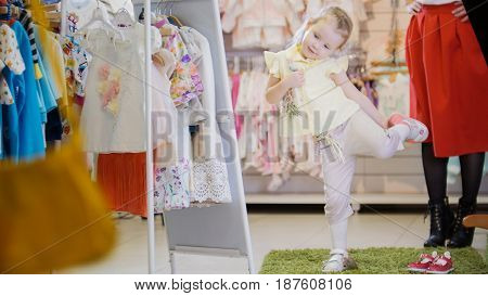 Little girl in a new summer suit and admires herself in the mirror in the children's clothing store