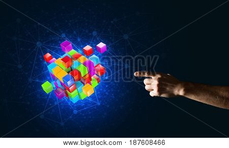 Close of man hand holding cube figure as symbol of innovation. Mixed media.