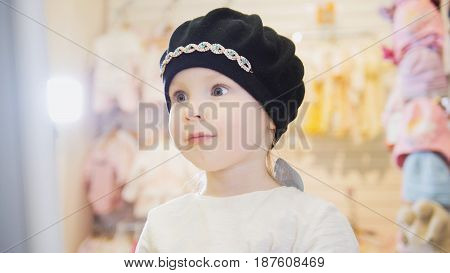 Cute girl in a black beret in front of a mirror in a clothing store for children