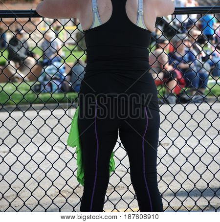 Overweight woman standing behind a fence outdoors.