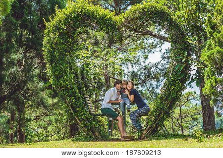 A Loving Family Under A Bush In The Form Of A Heart. St. Valentine's Day, Love Concept