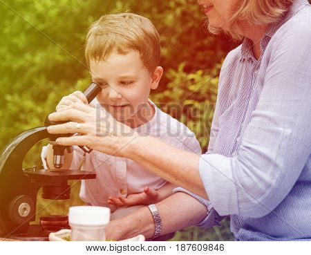 Grandson learning science microscope with grandparents