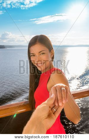 Newlyweds rings on honeymoon luxury cruise travel vacation holding hands. Man taking pov picture of Asian bride showing new diamond wedding bands together on cruise holidays in european destination.
