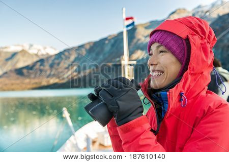 Alaska cruise travel woman looking at wildlife with binoculars. Tourist at Alaska Glacier Bay on ship. Woman on vacation looking at nature landscape enjoying cruising famous tourist destination.