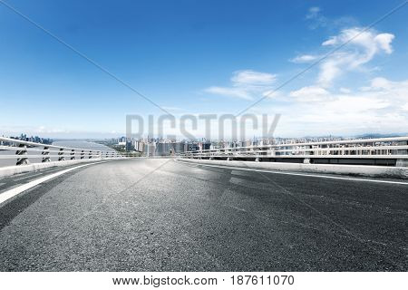 empty road with cityscape of modern city near river