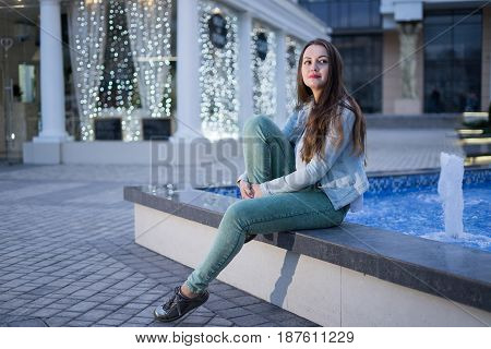 Alone beautiful girl sitting near fountain and dreaming looking on night city. She is waiting for somebody