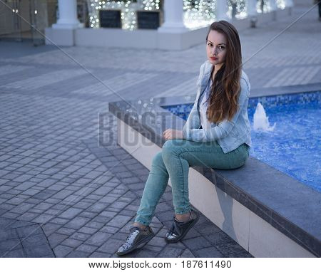 Alone beautiful girl sitting near fountain at night and looking at the camera. She has silver shoes