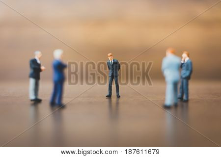 Miniature People Businessman On Wooden Background