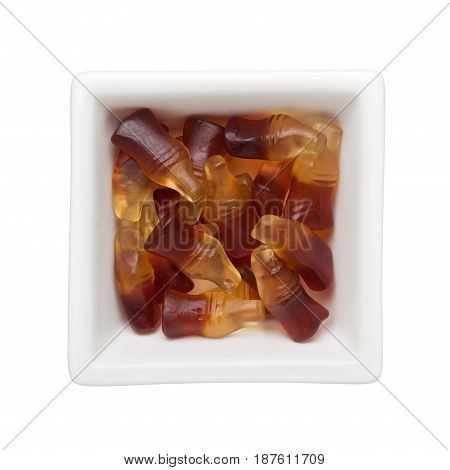 Cola flavored gummies in a square bowl isolated on white background
