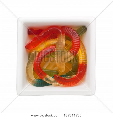 Worm shaped gummies in a square bowl isolated on white background