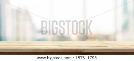 Wood table top on blur city building view background looking through glass window panoramic banner - can be used for display or montage your products