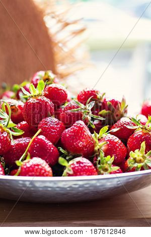 Dishes With Strawberries And Straw Hat In Sunlight.