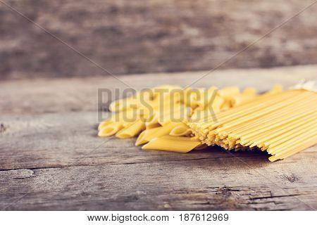 Macaroni, Pasta, Spaghetti On A Wooden Background.