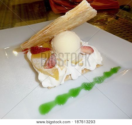 pastry topped with ice cream and strawberry slices Dessert of pastry slice topped with a scoop of vanilla ice cream and strawberry slices arranged on a white platter