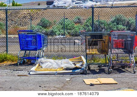 Three Shopping carts & Broken Box Spring In Parking Lot