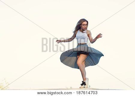 Young attractive hipster girl dancing against the sky. She wears glasses top skirt and sneakers. Skirt develops and hair flies. Beauty and youth.