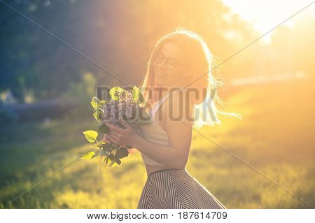Young attractive hipster girl holding a bouquet of lilac flowers. She wears glasses top skirt and sneakers. Cute smile. Walk outdoors. Warm toned. Backlight photography.
