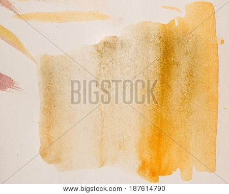 Abstract background of yellow brown watercolor paint. Drawing on wet paper. Flow of watercolor on paper. Element of design.