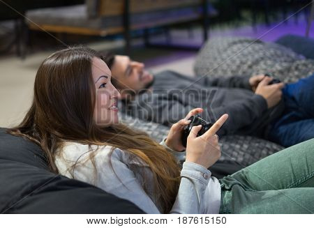 Portrait of happy couple friends playing video games with joystick sitting on Bean bag chair. Man and woman playing home video game console