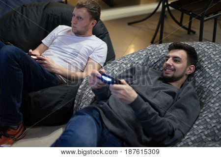 Portrait of two men friends playing video games with joystick sitting on Bean bag chair. They are interested of game. One man is winning