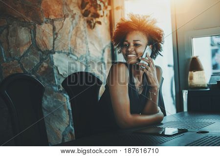 Charming young afro american curly girl in black dress talking on smartphone while waiting her colleagues in dark office room with stoned wall to discuss a new project during sunny summer day outside