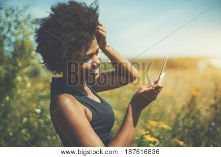 Young curly afro american female fixing her hair using frontal camera of her smart phone cute smiling black teenage girl making selfie on her mobile phone while standing on yellow summer meadow