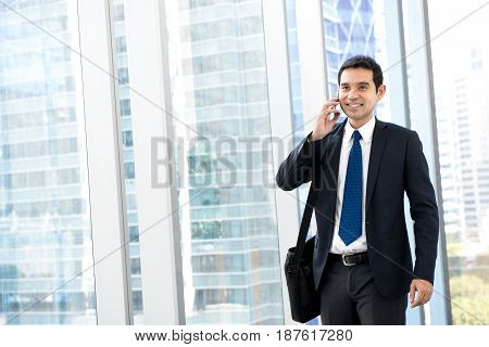 Handsome Asian businessman calling on mobile phone while walking in building hallway