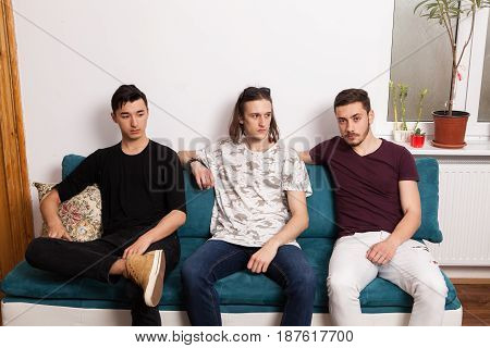 Three friends hanging out together in nice confortable room. Male friendship