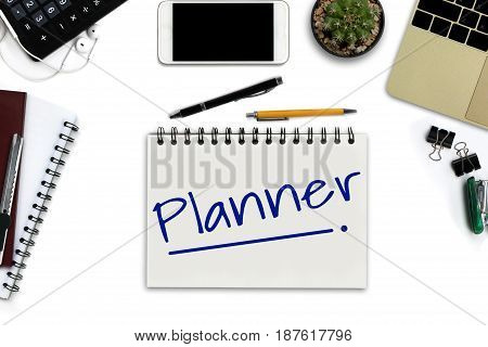 Planner on notepad - White office desk with smartphone with black screen pen laptop computer notepad and supplies. - Top view image.