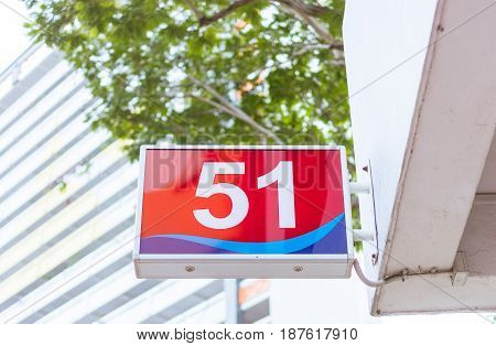Number 51 Sign Hung On Side Of A Building.