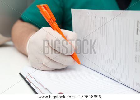 The doctor writes in a notebook at the clinic .