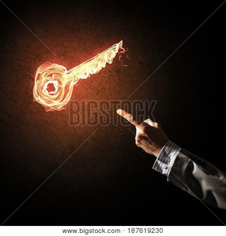 Close of businessman hand showing on fire glowing key symbol