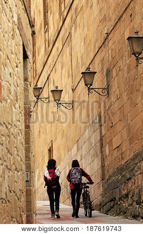 Salamanca, Spain - May 7, 2014. Two schoolgirls with backpacks and bicycle in narrow street of beautiful Salamanca.