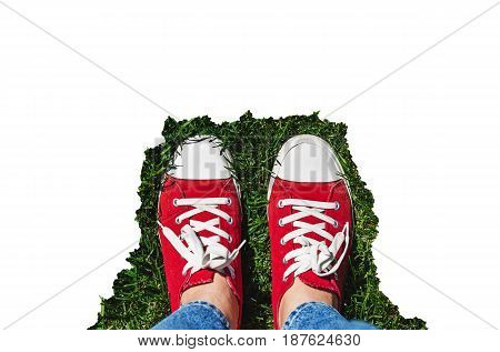 Legs In Old Red Sneakers On Green Grass. View From Above. The Concept Of Youth, Spring And Freedom.