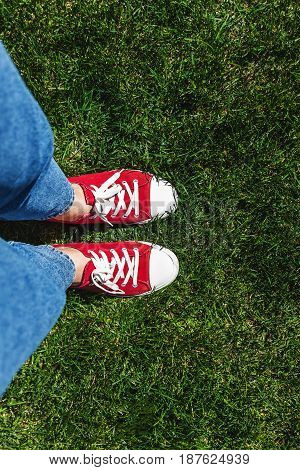 Legs In Old Red Sneakers On Green Grass. View From Above. The Concept Of Youth, Spring And Freedom