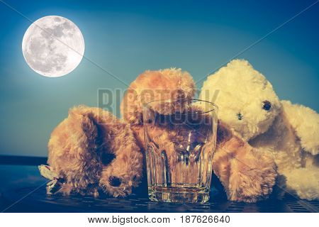 Teddy bears couple very drunk alcoholic and sleeping with empty glass on table blue sky and full moon background. Alcohol is not good for health and don't drink concept. Vintage effect tone.