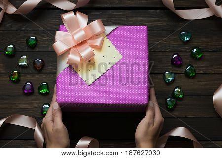 Gift box in hands on a dark wooden background