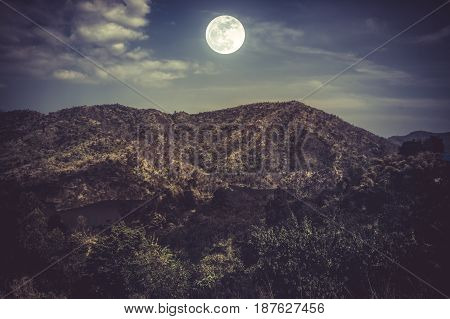 Landscape of blue dark night sky and cloudy above mountain peak. Beautiful bright full moon over tranquil nature. Vintage effect tone. The moon taken with my own camera.