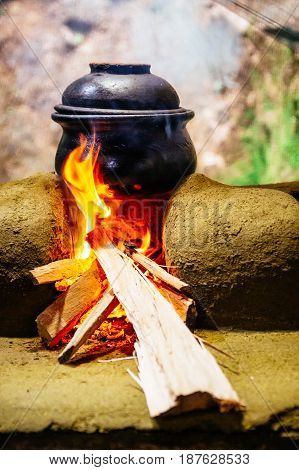 A Clay Pot Cooking And Heated Over A Wood Fired Stove Made Out Of Mud And Clay In A Traditional Outd