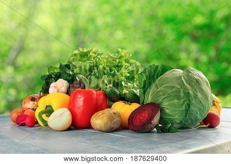 Different raw fresh vegetables оn a blue rustic wooden table. Healthy eating