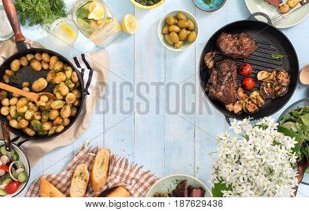 Frame of grilled steak vegetables potatoes salad snacks homemade lemonade on blue rustic wooden table