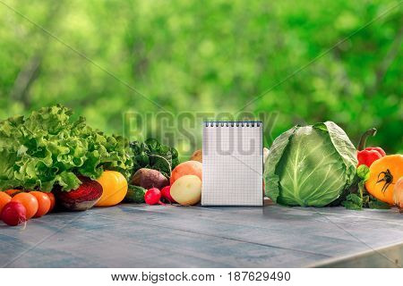 Set of different fresh vegetables with blank notepad on a blue wooden table on a background of green bokeh leaves