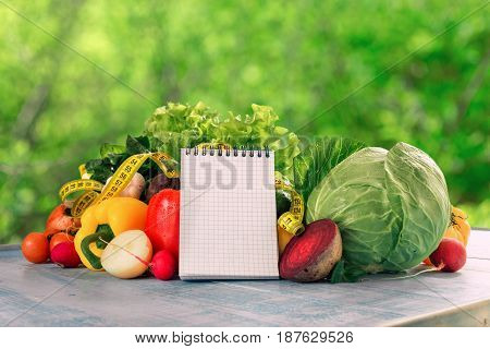 Set of different fresh vegetables with measuring tape and blank notepad on a blue wooden table on a background of green bokeh leaves